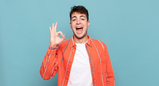 Młody mężczyzna czuje się zadowolony i odnosi sukcesy, uśmiechając się z szeroko otwartymi ustami, robiąc dobry znak ręką