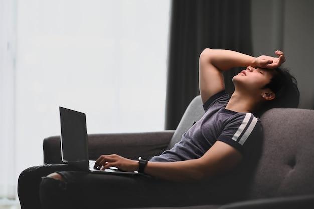 Młody mężczyzna czuje się zmęczony pracą online, siedząc na kanapie w domu