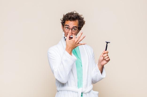 Młody mężczyzna czuje się zniesmaczony, trzyma nos, żeby nie poczuć obrzydliwego i nieprzyjemnego smrodu