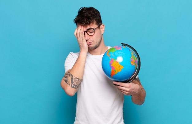 Młody mężczyzna czuje się znudzony, sfrustrowany i senny po męczącym, nudnym i żmudnym zadaniu, trzymając twarz dłonią
