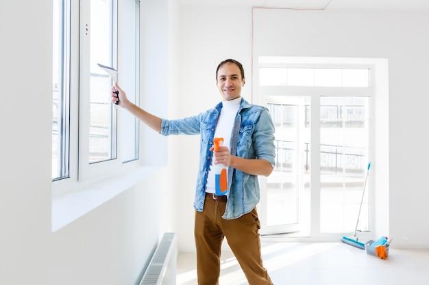 Młody mężczyzna czyści okno w biurze