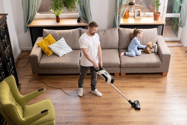Młody mężczyzna czyści podłogę w salonie odkurzaczem, podczas gdy jego urocza córeczka w piżamie bawi się z misiem na kanapie w pobliżu
