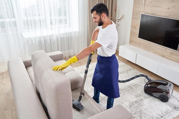 Młody mężczyzna czyszczenie sofy z odkurzaczem w wychodzeniu z pokoju w domu
