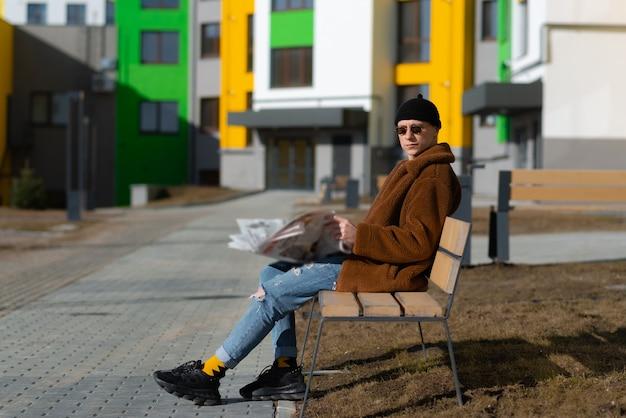 Młody mężczyzna czyta gazetę na ławce w parku