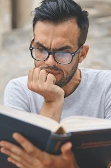 Młody mężczyzna czyta książkę w kampusie