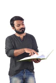 Młody mężczyzna, czytanie lub posiadanie książki lub pamiętnika na białym tle.
