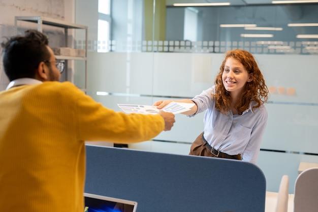 Młody mężczyzna daje dokumenty statystyczne pozytywnej ładnej damie z kręconymi włosami, gdy razem pracują nad raportem sprzedaży w biurze