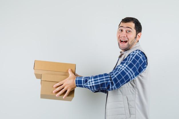 Młody mężczyzna daje pudełka komuś w koszuli, kurtce i patrząc wesoło, widok z przodu.