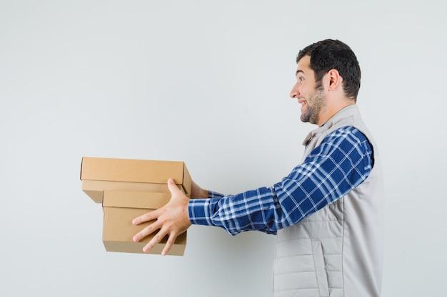 Młody mężczyzna daje pudełka komuś w koszuli, kurtce i wyglądający wesoło, widok z przodu.
