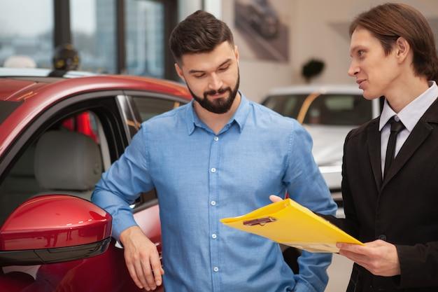 Młody mężczyzna dealer samochodowy rozmawia ze swoim klientem płci męskiej