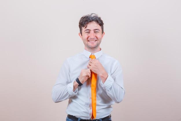 Młody mężczyzna dopasowujący krawat w koszuli, dżinsach i wyglądający na szczęśliwego