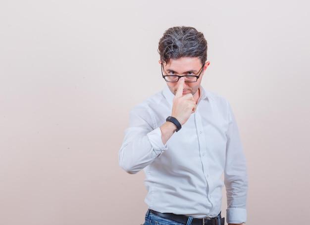 Młody mężczyzna dopasowujący okulary w białej koszuli, dżinsach i wyglądający poważnie