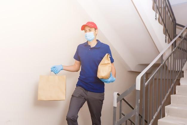 Młody mężczyzna dostarczający jedzenie do klienta w drzwiach