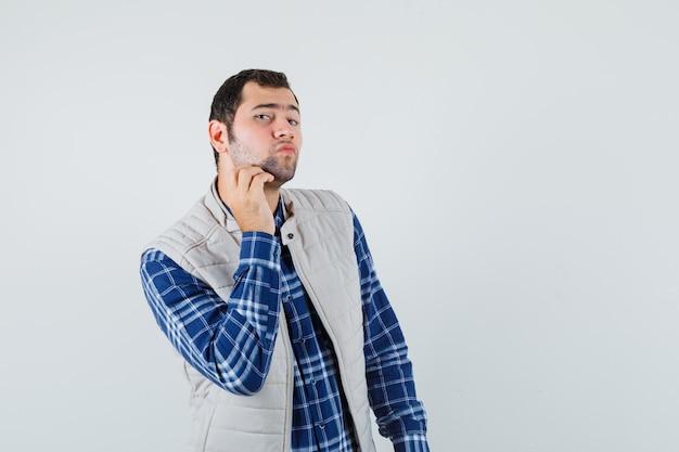 Młody mężczyzna dotykając brodę w koszuli, widok z przodu kurtka bez rękawów.