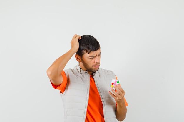 Młody mężczyzna drapie się po głowie patrząc na kostkę rubika w t-shirt, marynarce i wygląda na zakłopotanego.