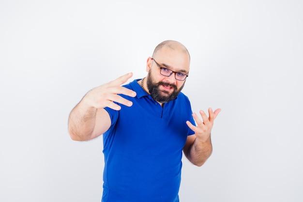 Młody mężczyzna dyskutuje pokazując gesty rąk w niebieskiej koszuli, okularach i patrząc rozmowny. przedni widok.