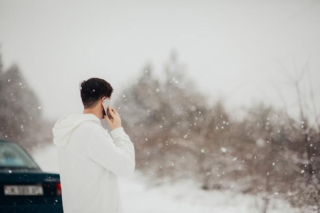 Młody mężczyzna dzwoni do serwisu samochodowego. ma problem z samochodem w zimowy śnieżny dzień.