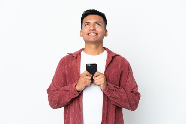 Młody mężczyzna ekwadoru na białym tle na białej ścianie przy użyciu telefonu komórkowego i patrząc w górę