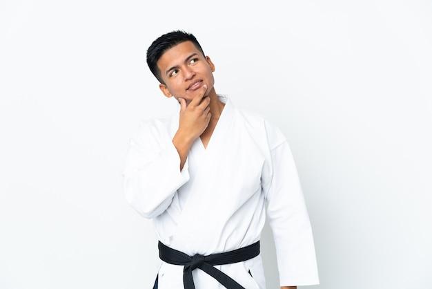 Młody mężczyzna ekwadoru robi karate na białym tle na białym tle patrząc uśmiechnięty