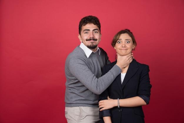 Młody mężczyzna figlarnie dusi kobietę na czerwonej ścianie