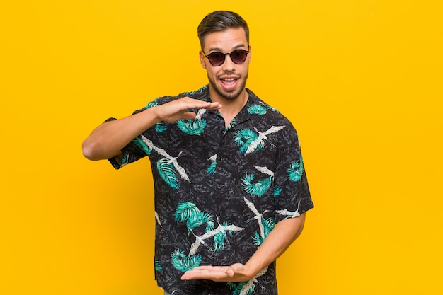 Młody mężczyzna filipina na sobie letnie ubrania trzyma coś obiema rękami, prezentacja produktu.