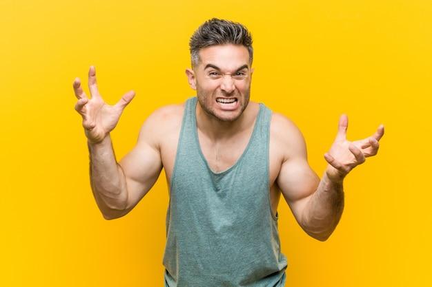 Młody mężczyzna fitness na żółtym tle krzyczy z wściekłości.