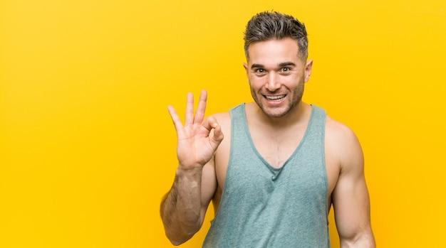 Młody mężczyzna fitness na żółtym tle mruga okiem i trzyma w porządku gest ręką.