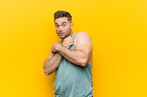 Młody mężczyzna fitness na żółtym tle przestraszony i przestraszony.