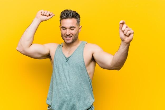 Młody mężczyzna fitness na żółtym tle świętuje wyjątkowy dzień, skacze i energicznie podnosi ramiona.
