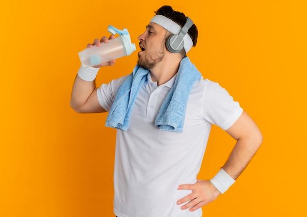 Młody mężczyzna fitness w białej koszuli z pałąkiem na głowę i ręcznikiem wokół szyi, trzymając butelkę wody pitnej po treningu stojąc na pomarańczowym tle