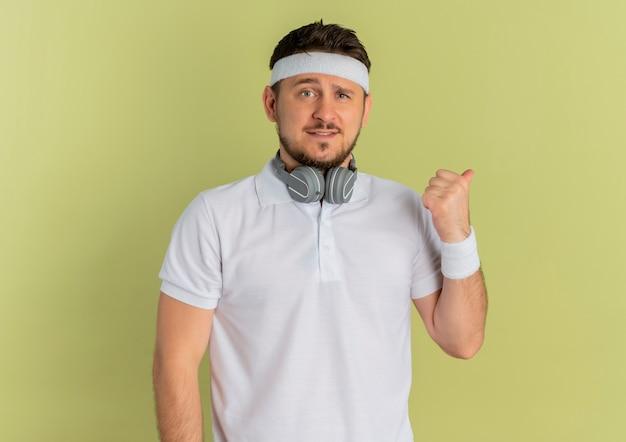 Młody mężczyzna fitness w białej koszuli z pałąkiem na głowę, patrząc do przodu, uśmiechając się i wskazując kciukiem w bok, stojąc na ścianie oliwnej