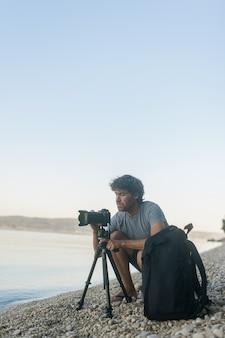 Młody mężczyzna fotograf na plaży ustawia aparat na statywie, aby zagrać w sesji zdjęciowej.