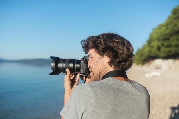 Młody mężczyzna fotograf robi zdjęcia pięknego morza i przyrody wczesnym rankiem swoim profesjonalnym aparatem dslr.
