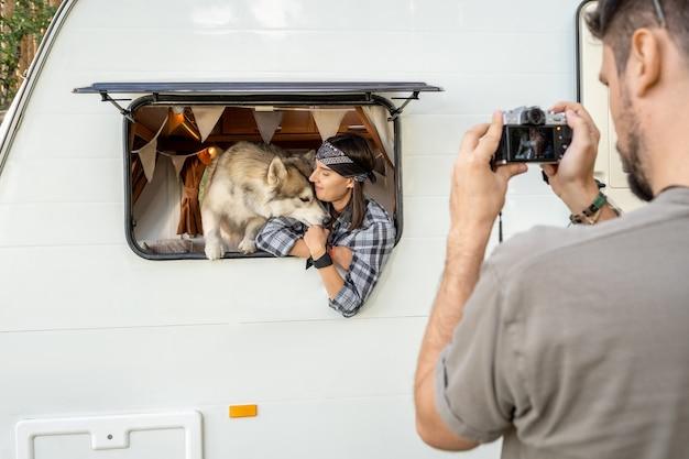 Młody mężczyzna fotografuje swoją żonę i psa husky