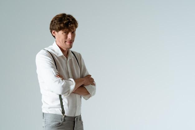 Młody mężczyzna foxy z rękami założonymi na piersi. na białym tle na białej ścianie. skopiuj miejsce.