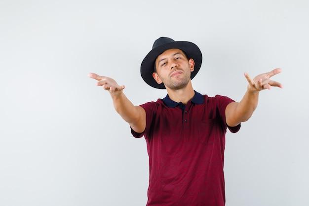 Młody mężczyzna gestykulujący, jak odbieranie lub przekazywanie czegoś w koszulce, kapeluszu, widok z przodu.
