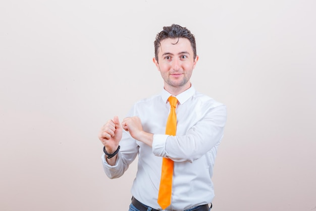 Młody mężczyzna gestykulujący, jakby przygotowywał się do wypuszczenia strzały w białej koszuli, dżinsach