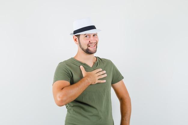 """Młody mężczyzna gestykulujący, pytający """"ja""""? w zielonej koszulce i czapce i nieśmiało"""