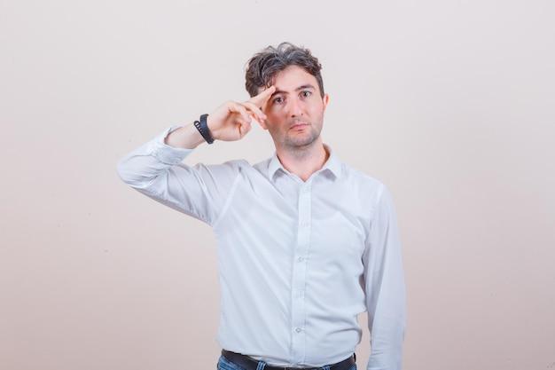 Młody mężczyzna gestykuluje ręką i palcami w białej koszuli, dżinsach i wyglądającym pewnie