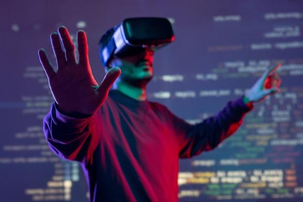 Młody mężczyzna gestykuluje rękami podczas analizowania kodu programowania w goglach wirtualnej rzeczywistości