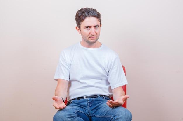 Młody mężczyzna gestykuluje siedząc na krześle w koszulce, dżinsach i wygląda na zdezorientowanego