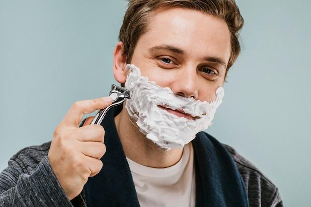 Młody mężczyzna golący brodę