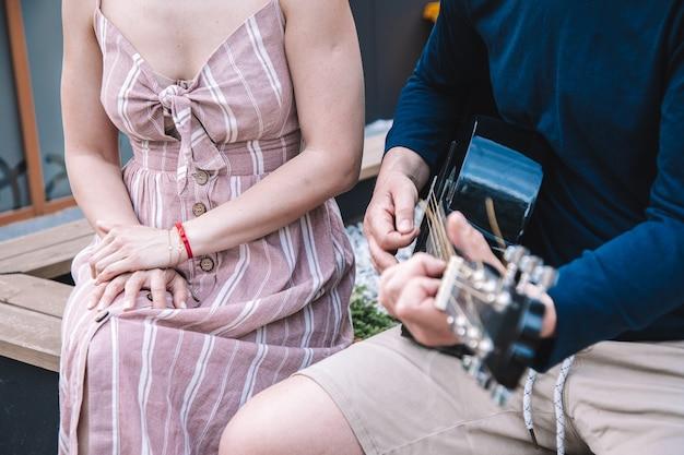 Młody mężczyzna gra dla swojej młodej kobiety. pojęcie muzyki w naszym życiu. piękne momenty . styl życia. zdjęcie wysokiej jakości