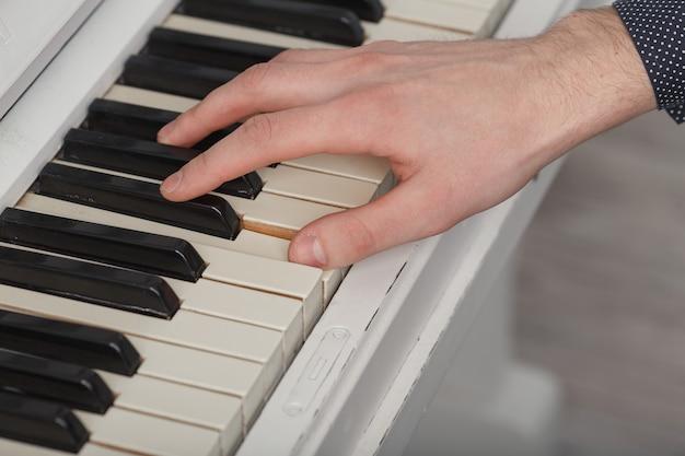 Młody mężczyzna gra na fortepianie zbliżenie. koncepcja muzyki i hobby