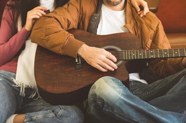 Młody mężczyzna gra na gitarze do swojej pięknej dziewczyny siedząc na podłodze w salonie