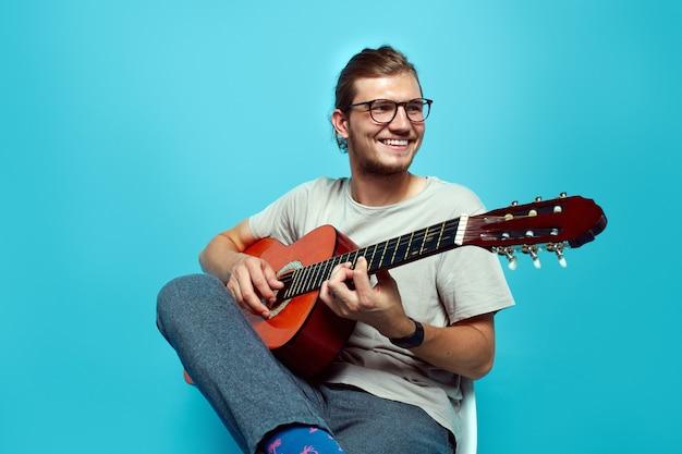 Młody mężczyzna gra na gitarze siedząc na białym tle nad niebieską ścianą