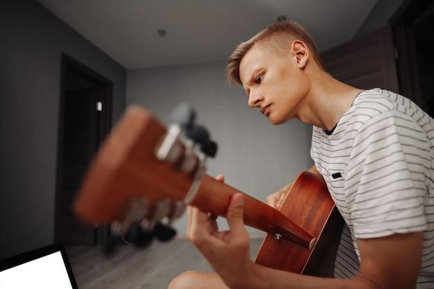 Młody mężczyzna gra na gitarze w domu