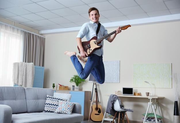 Młody mężczyzna gra na gitarze w pokoju