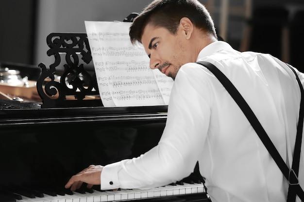 Młody mężczyzna gra na pianinie w pomieszczeniu