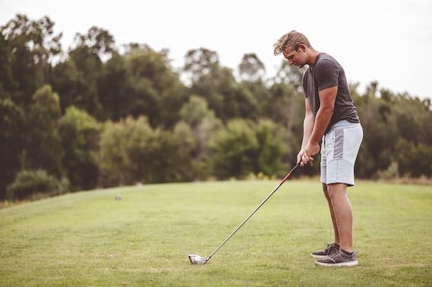 Młody mężczyzna gra w golfa